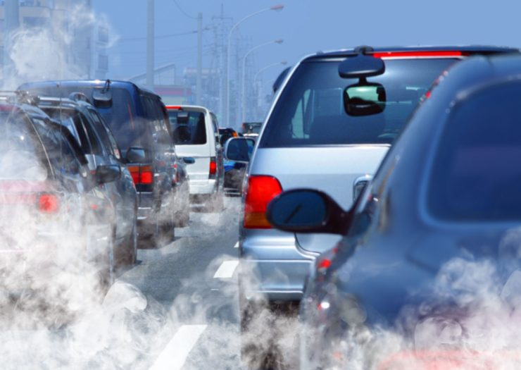 a traffic jam of cars and their exhaust stresses a bicycling benefit of reduced carbon emissions