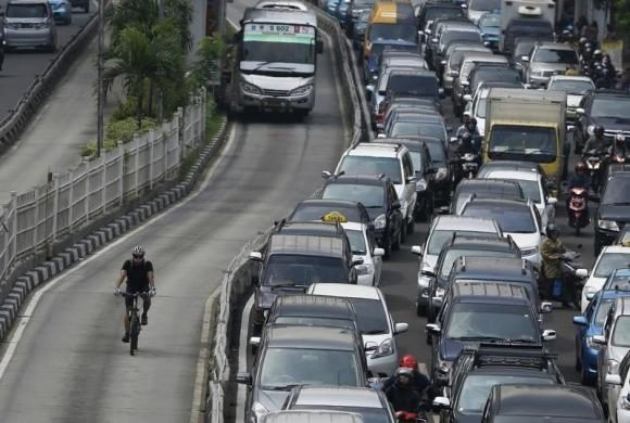 a bicycler enjoys a benefit of biking by pedaling around a traffic jam