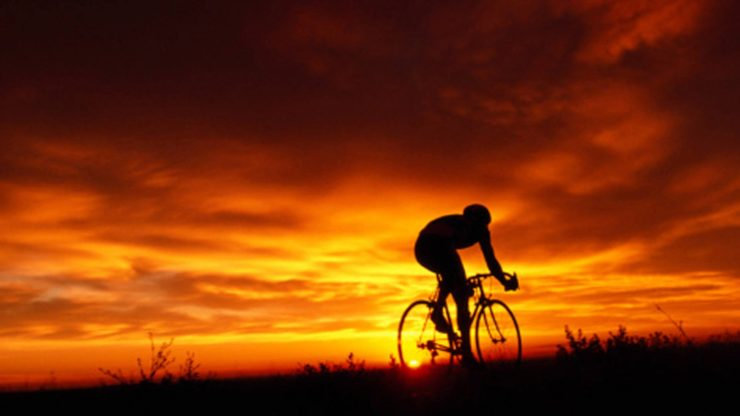 a rider enjoys the health benefits of biking solo at sunset