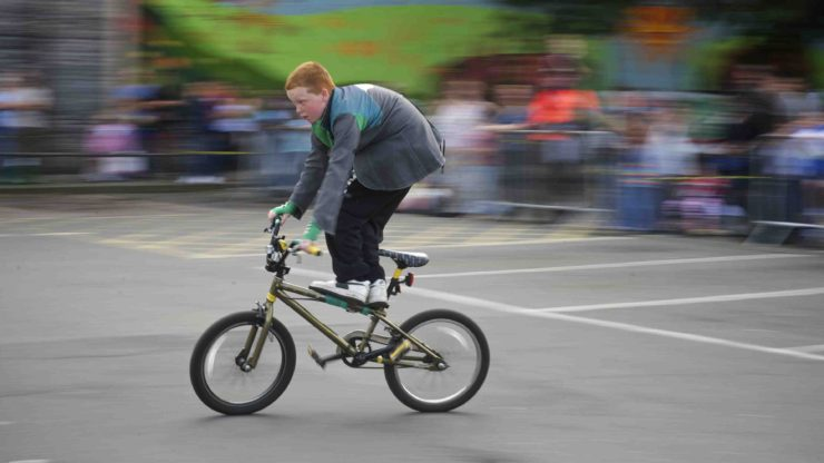 a boy stands on his bicycle showing improved balance as a benefit of biking