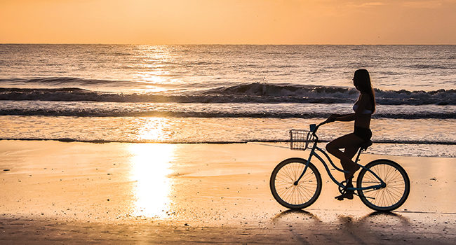 a bicycler enjoys the benefits of biking on a sunrise beach cruise