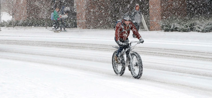 a bicycler riding in the snow shows that health benefits of bicycling are year round