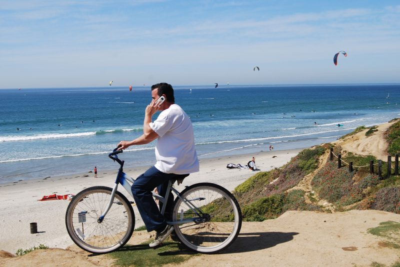 man on cruiser bicycle by ocean